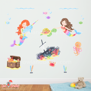 Part of the large mermaid fabric wall decals scene by Owl and Brolly. A close up view of 2 mermaids, the treasure chest, the ship wreck with fish, and other seaweeds and underwater creatures.
