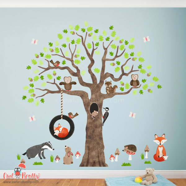 Woodland animal tree wall sticker decals wall art, for a neutral gender nursery room theme of decor. Featuring a large oak tree decal with lots of woodland animals including a sleeping fox, badger, bunny, hedgehog and owl decals. Easy to peel and stick and place to create a theme in your child's room.